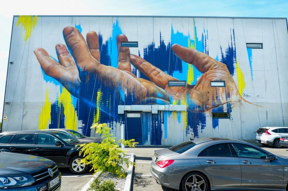 Mural by Adnate of two hands with open palms on Kilmore Street in Christchurch