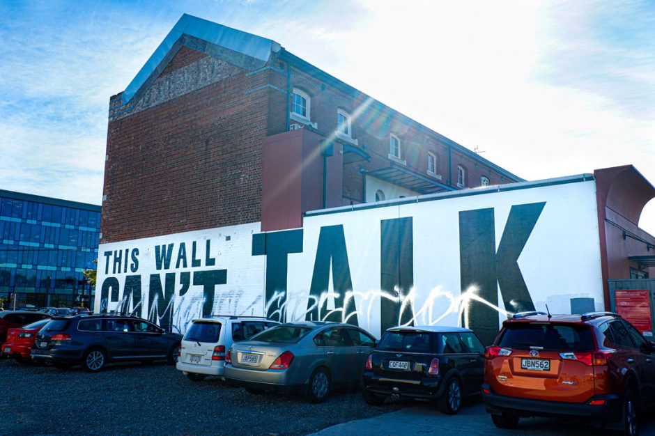 Large black text on a white wall saying in bold black letters: This Wall Can't Talk
