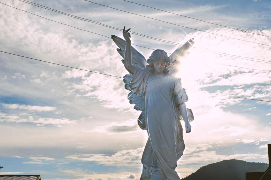 large white sculpture of an angel by the entrance of St Faith's Anglican Church