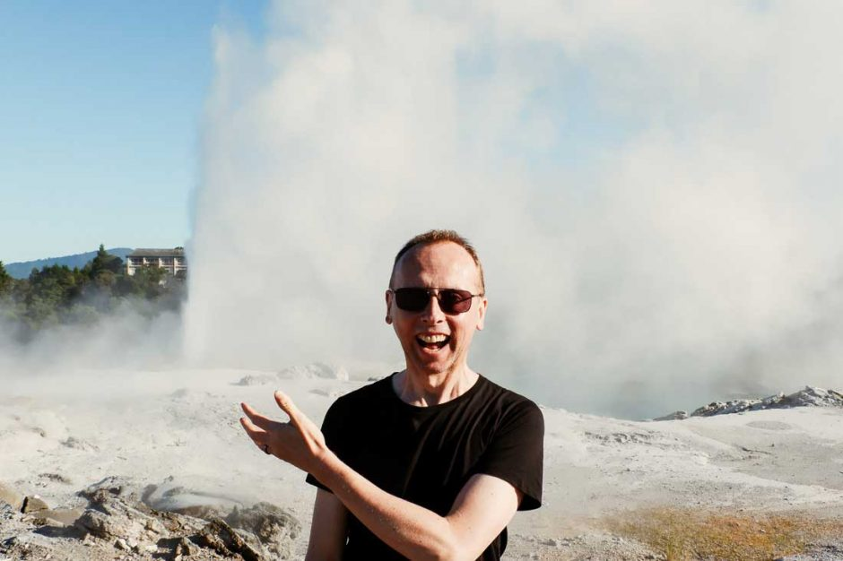 my husband smiling and gesturing at the geyser erupting behind him in Te Puia geothermal park in Rotorua