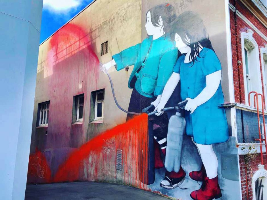 Mural of two girls spraying paint on the wall and street
