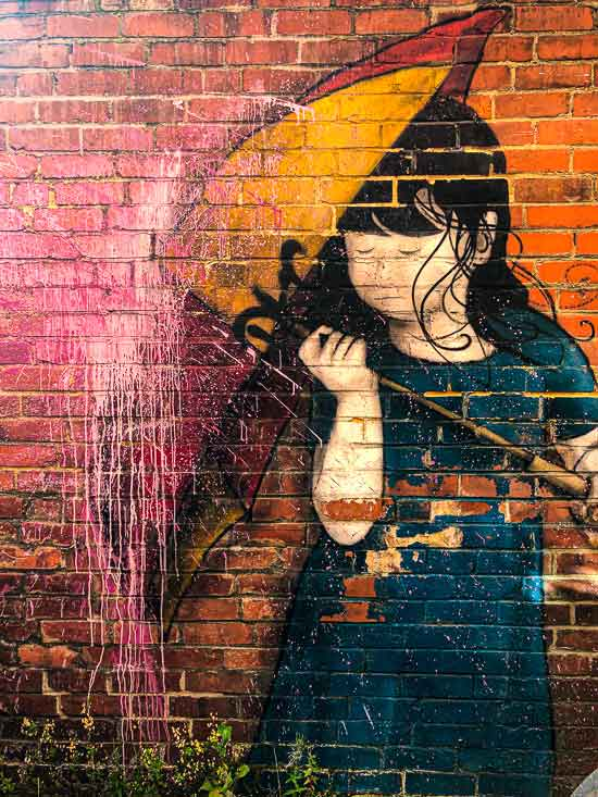 mural of a girl holding an umbrella to stop paint hitting her head