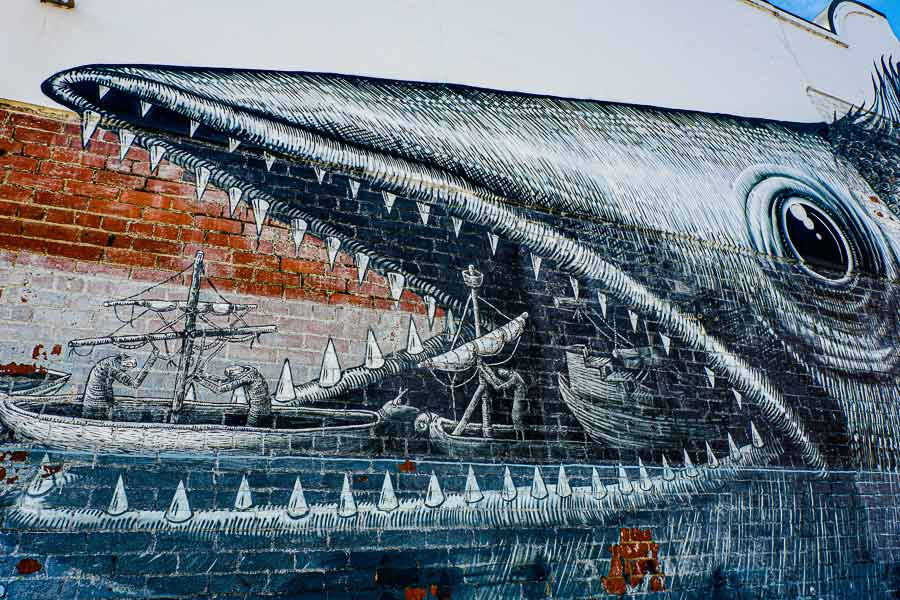 close-up of the mural by Phlegm with the wooden vessels entering the fish's mouth