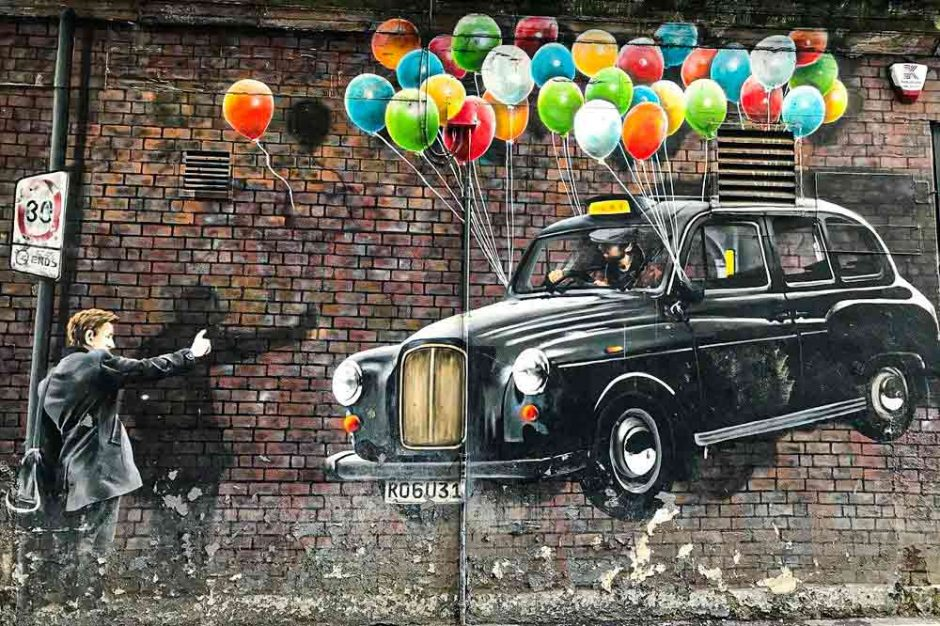 street art in Glasgow by Rogue One of a taxi floating in the air by balloons