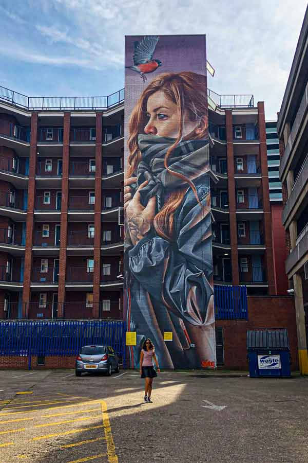street art in Leicester by Smug very tall portrait of a young woman in a council estate