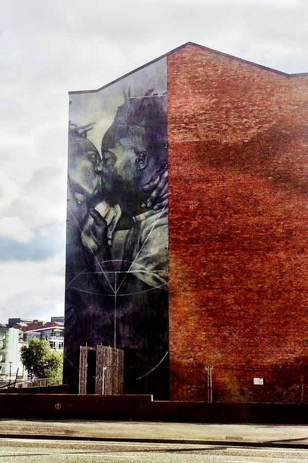 street art in Manchester by Faith47 of two men kissing
