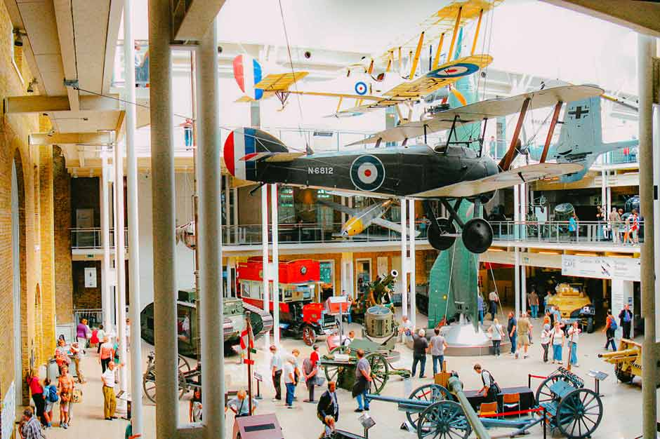 Hall of the Imperial War Museum London with a fighter plane hanging from the ceiling and several old vehicles on the ground