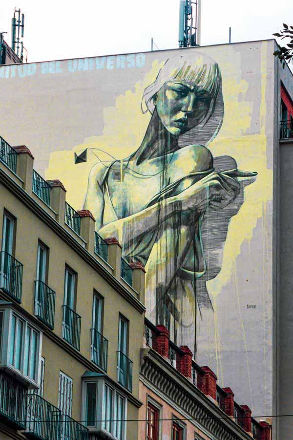Large mural of a woman by Faith47 in Málaga on an apartment building