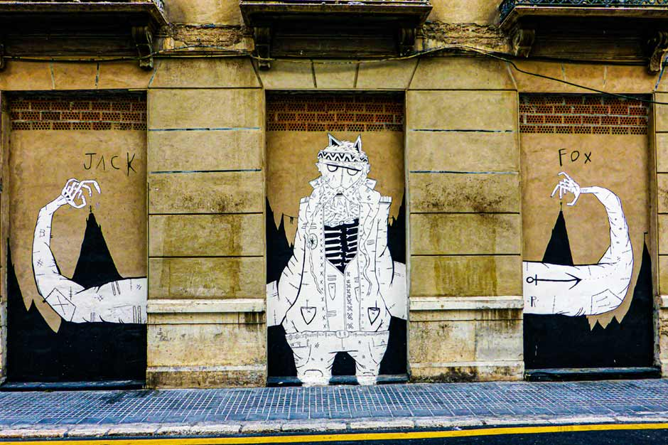 Street art by Jack Fox of a man with really long arms flexing his muscles
