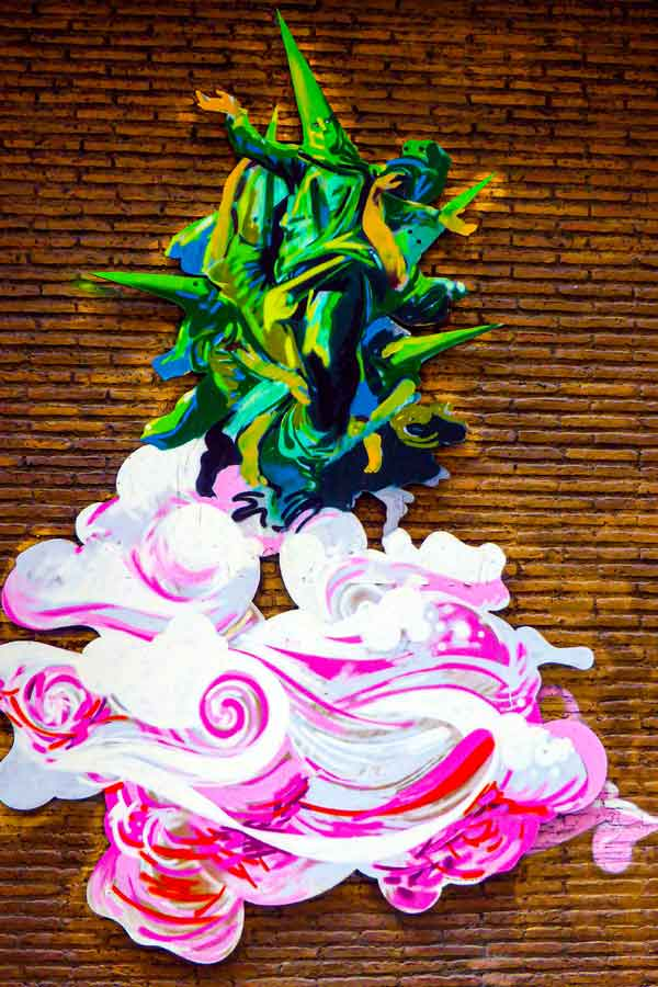 Street art by Manuel Léon depicting people wearing semana santa outfits