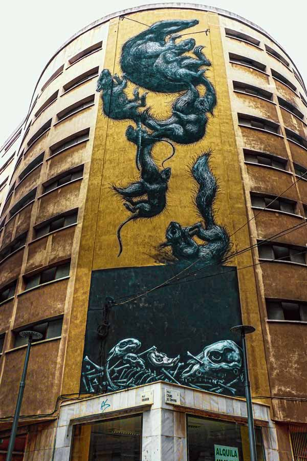 Large mural by ROA in Málaga of several animals on the side of an abandoned building
