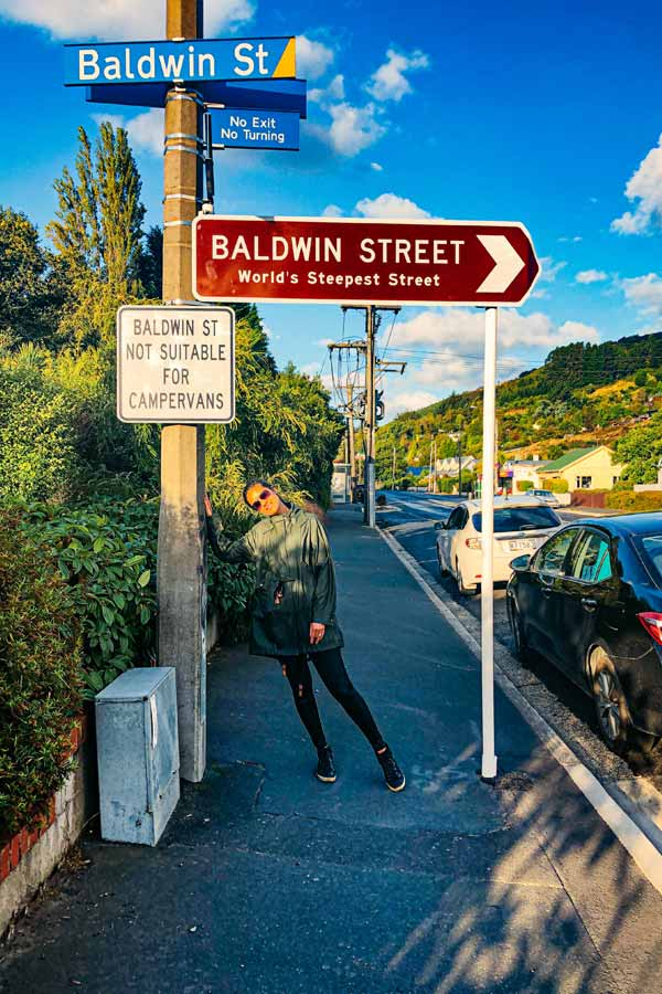 Zarina standing by the sign for Baldwin Street in Dunedin, New Zealand, the world's steepest street