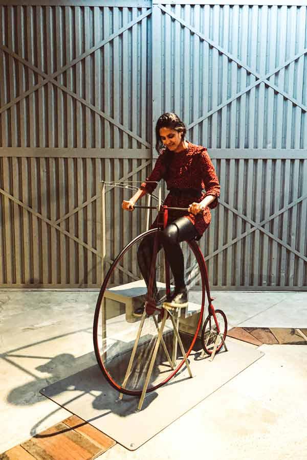 Zarina on a historical penny-farthing bike in the Otago Settlers Museum in Dunedin, New Zealand