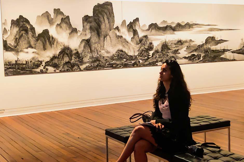 Zarina sitting in front of a Xu Zhen artwork in Dunedin Public Art Gallery