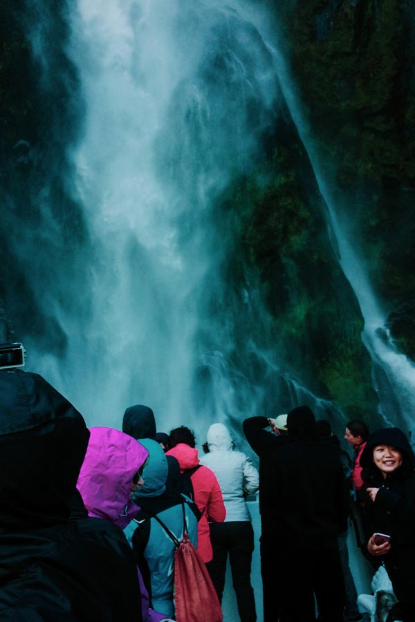 our fellow passengers getting soaked by a waterfall on the Milford Sound boat cruise
