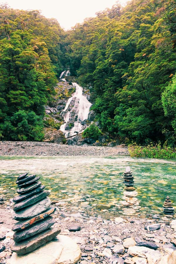 Fantails Falls in New Zealand in the background with rock stacks by humans in the foreground