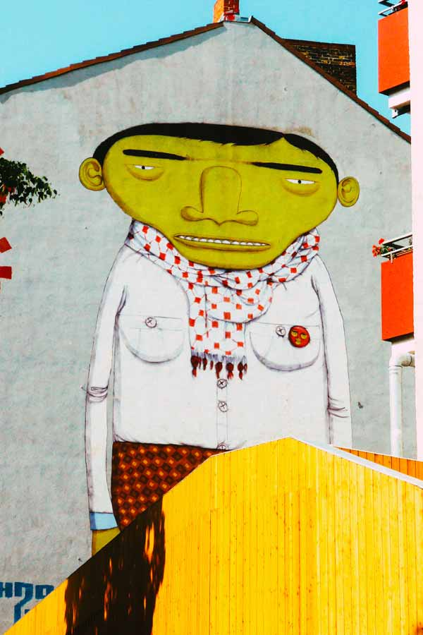wall painting by twins Os Gemeos of a large yellow man in Kreuzberg