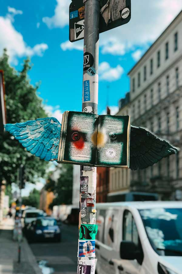 street art in Auguststrasse in Mitte, Berlin of a book stuck to a traffic sign with angel wings