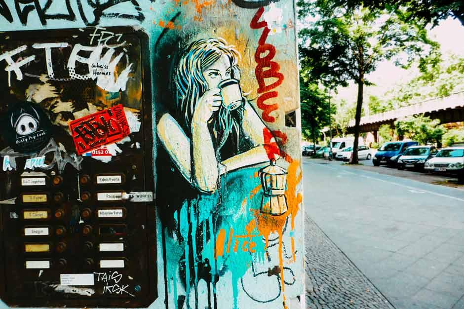Alice Pasquini stencil artwork of a woman drinking coffee in Kreuzberg