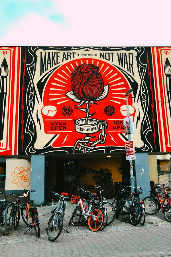 mural by Shepard Fairey with the text 'Make art not war' with large paint brushes and a shackled red rose with the text 'Rise above'