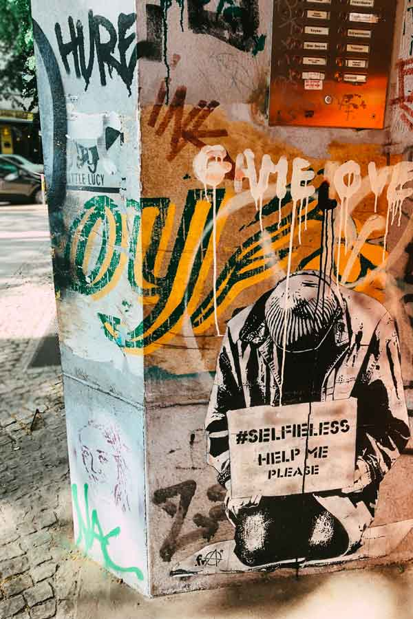 Paste-up on Intimes Kino of a seemingly homeless man holding a sign Selfieless, Help me please
