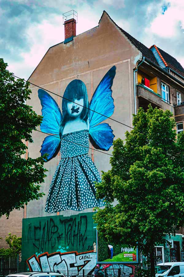 mural of a large blue girl with butterfly wings by Michele Tombolini in Friedrichshain