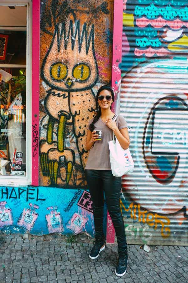 Zarina posing my a mural of an owl by Dscreet