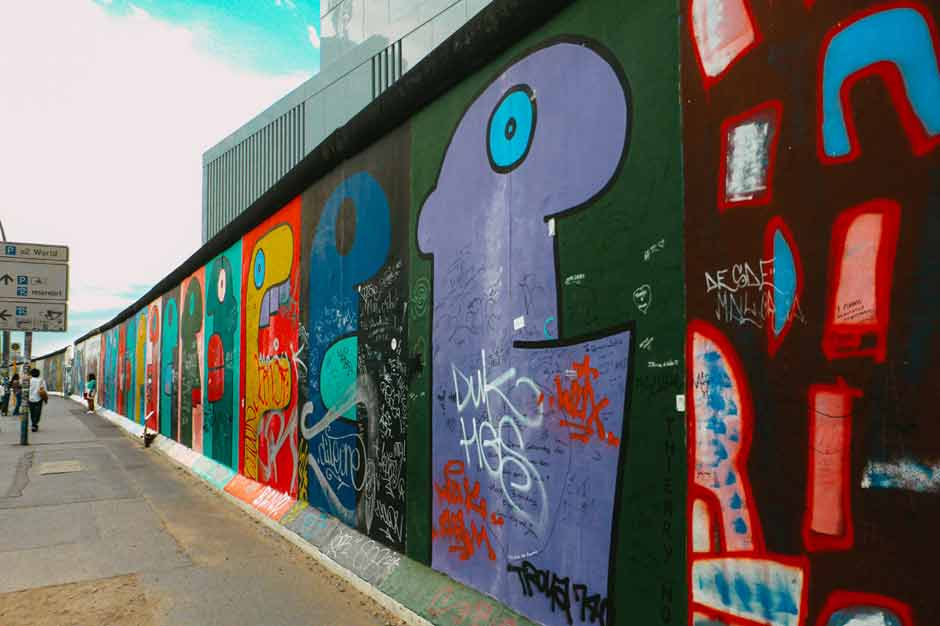 series of murals by Thierry Noir of his signature giant cartoon heads in bold colours