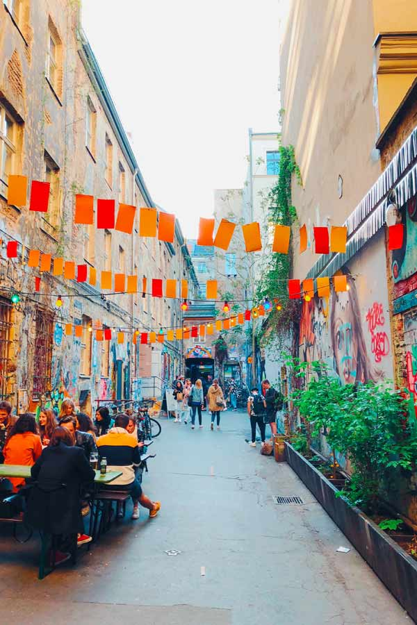 looking into the alley of Haus Schwarzenberg which is a real street art hotspot in Berlin recognisable by the red and orange buntings