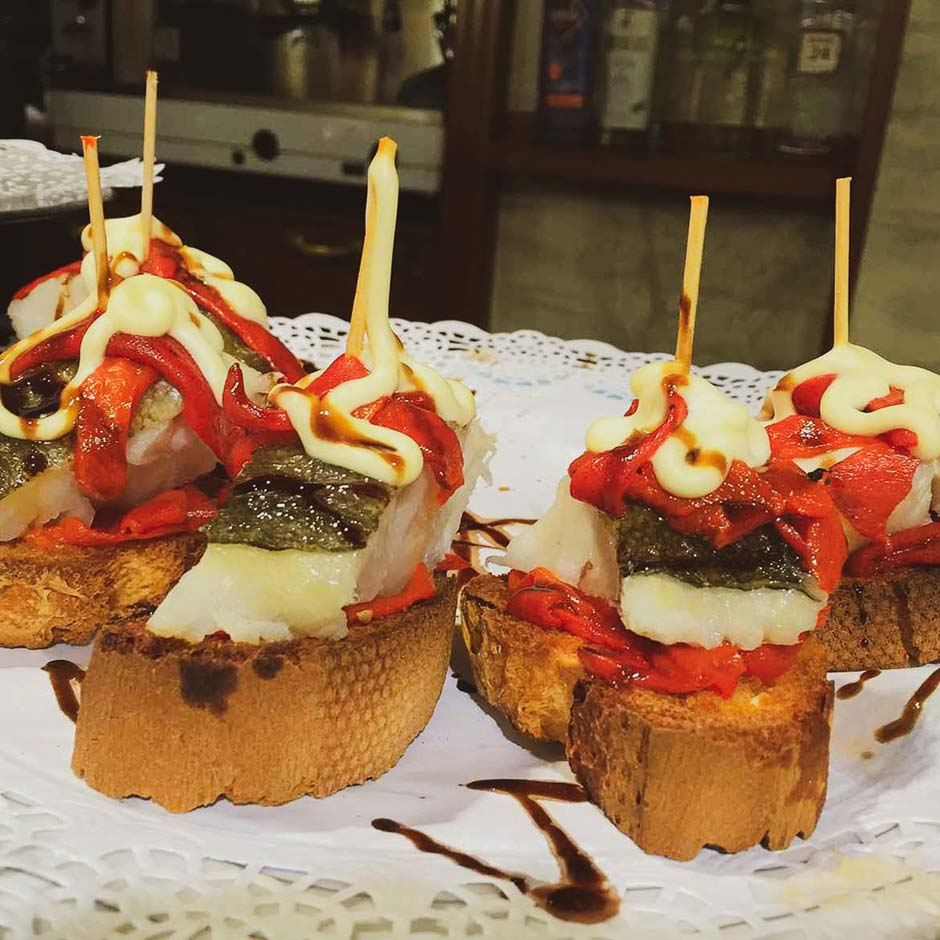 Plate of pinchos with cod and marinated pepper