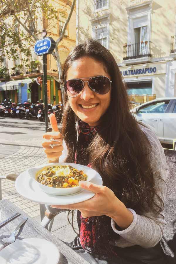 Zarina holding a dish of espinacas con garbanzos at Dos de Mayo