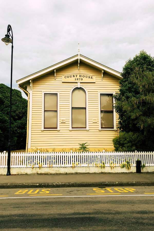 Yellow exterior of the former 19th-century courthouse in Akaroa, New Zealand