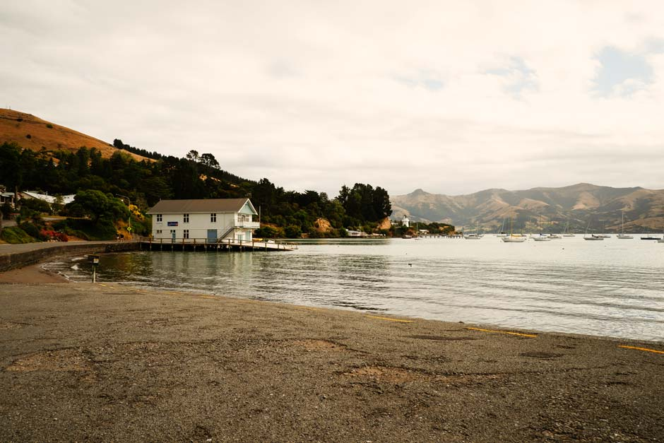 idyllic view of a boat house on Akaroa beach surrounded by montains and golden coloured trees