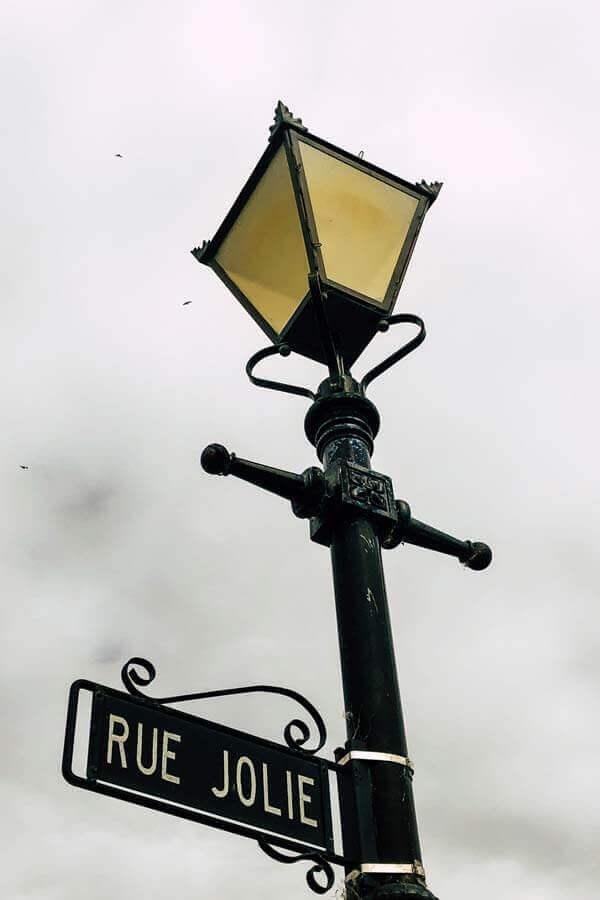 Close-up of the street sign Rue Jolie underneath a pretty streetlight in historic French settlement Akaroa, New Zealand