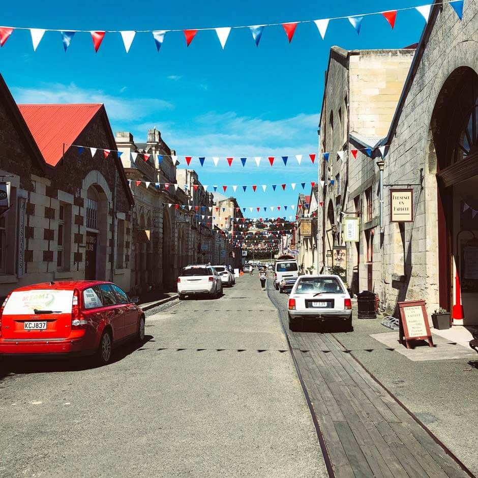 streetview of Oamaru with festive bunting hanging in street with historic stone buildings