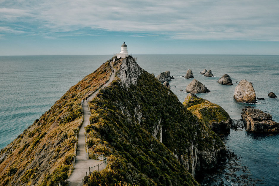 looking out over the Nugget Point Lighthouse located at the end of a thin stretch of land with rocks sticking out from the water beneath