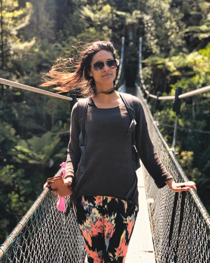 Zarina walking over a swing bridge during the Queen Charlotte Track in New Zealand