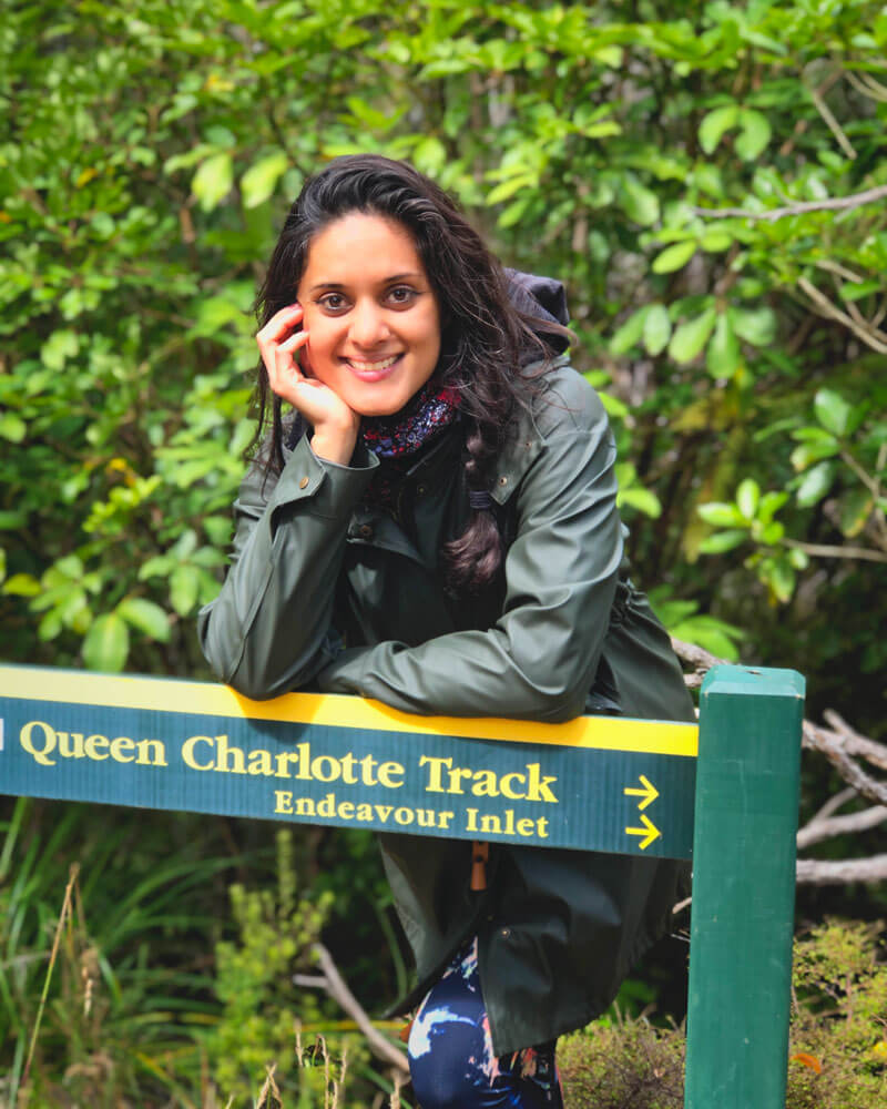 Zarina posing by a sign for the Queen Charlotte Track in Marlborough Sounds in New Zealand