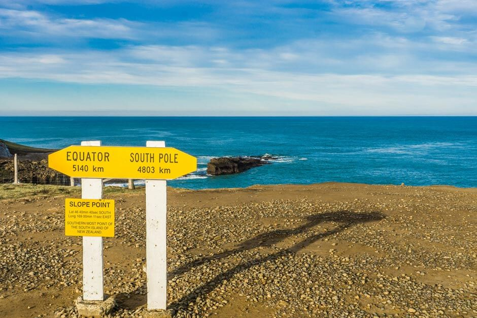 yellow sign at Slope Point with an arrow point left saying Equator 5140 km and an arrow pointing right saying South Pole 4803 km
